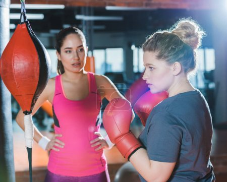 overweight woman having boxing training while trainer watching her