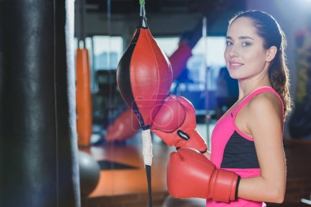 sporty woman in boxing mitts looking at camera
