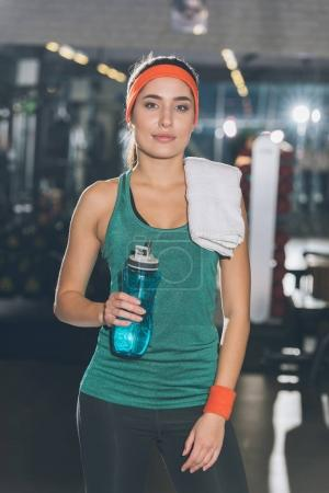 sporty woman standing with bottle and towel in hands at gym