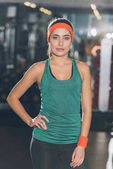 sporty woman standing at gym with hand on waist and looking at camera