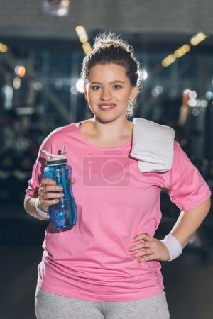 overweight woman standing with towel and bottle of water and looking at camera