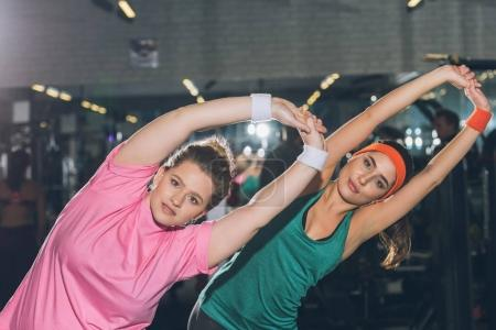 women at gym doing stretching exercises