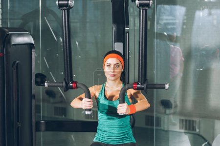 sporty woman working out on training apparatus at gym