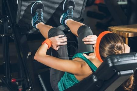 sporty woman training legs on training apparatus at gym