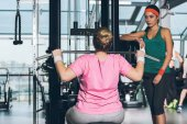 overweight woman working out on training apparatus while trainer watching her