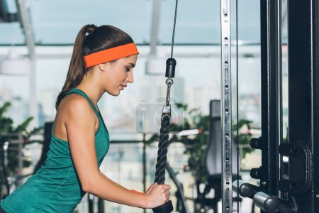 sporty woman exercising on training apparatus  at gym