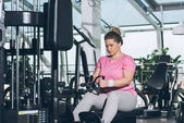 overweight woman working out on training apparatus