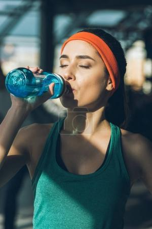 sporty woman drinking water at gym with closed eyes
