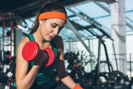 sporty woman working out with dumbbell at gym