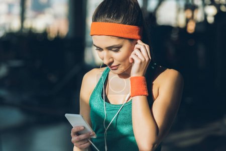 sporty woman using smartphone and earphones at gym