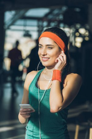 smiling woman using smartphone and earphones at gym