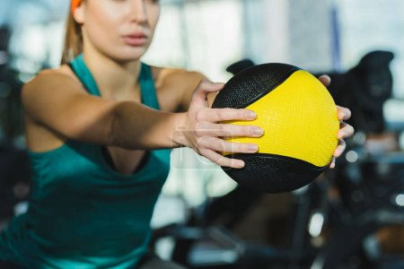 cropped image of sporty woman training with medicine ball at gym
