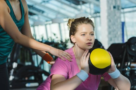 Photo for Overweight woman training with medicine ball while trainer helping her - Royalty Free Image