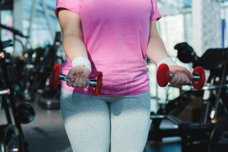 midsection of overweight woman with dumbbells at gym