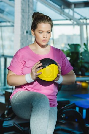 overweight woman training with medicine ball at gym