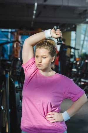 overweight woman training with dumbbell at gym