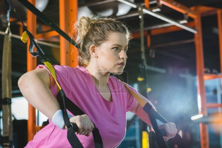 Photo for Overweight woman training on resistance bands at gym - Royalty Free Image