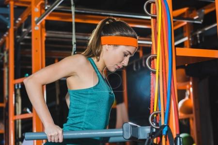 sporty woman training on beams at gym