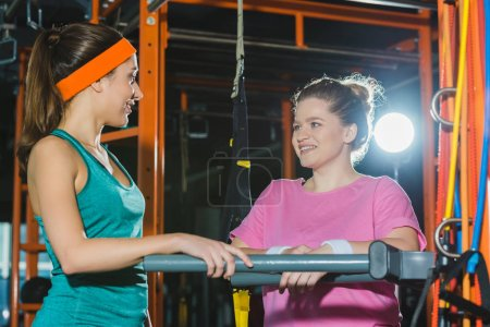 sporty woman standing against beams and smiling to overweight woman