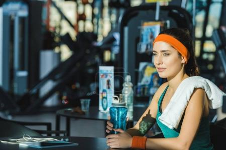 sporty woman sitting at table at gym with bottle of water