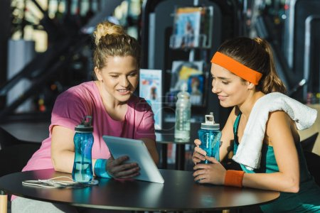 women sitting at table and looking on digital tablet at gym