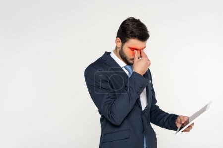 tired young businessman with pain in eyes holding digital tablet isolated on grey