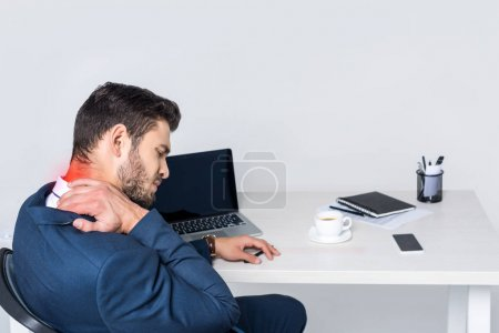 Photo for Young businessman suffering from pain in neck while sitting at workplace - Royalty Free Image