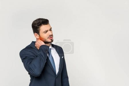 young businessman with closed eyes suffering from pain in neck isolated on grey