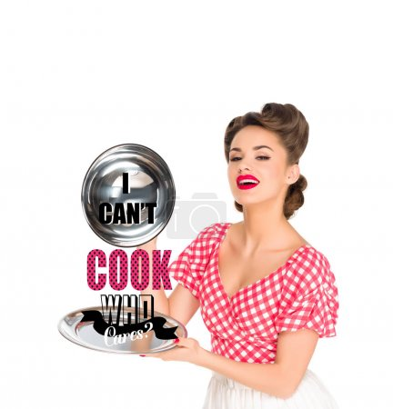 beautiful young woman in retro clothing with I CAN`T COOK, WHO CARES? lettering on serving tray in hands isolated on white