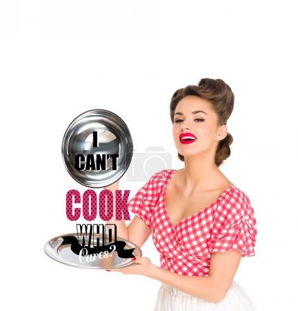 Photo for Beautiful young woman in retro clothing with I CAN`T COOK, WHO CARES? lettering on serving tray in hands isolated on white - Royalty Free Image