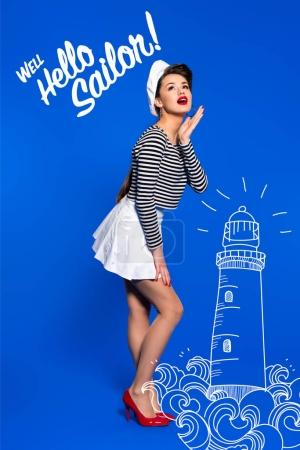 beautiful young woman in sailor shirt with lighthouse drawing and well hello sailor inscription isolated on blue