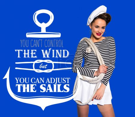 smiling beautiful young woman in sailor shirt with rope and motivational inscription isolated on blue