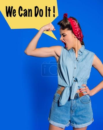 young woman in retro clothing showing muscles and shouting with we can do it speech bubble isolated on blue