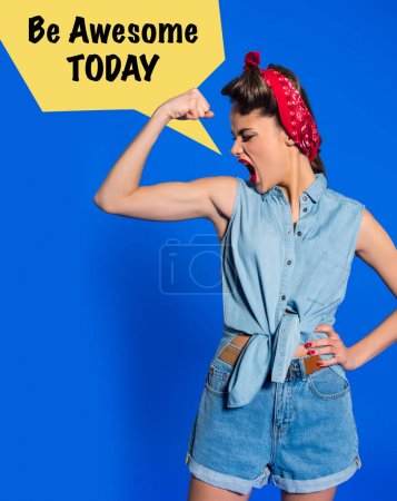 young woman in retro clothing showing muscles and shouting with be awesome today speech bubble isolated on blue