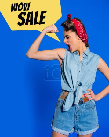young woman in retro clothing showing muscles and shouting with sale speech bubble isolated on blue