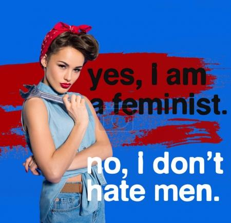 fashionable young woman in pin up style clothing with wrench and feminism quote