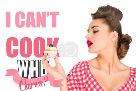 Photo for Portrait of beautiful woman in pin up clothing with cupcake and I CAN`T COOK, WHO CARES? lettering isolated on white - Royalty Free Image