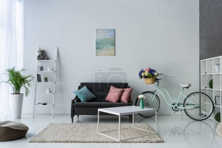 Photo for View of stylish living room with retro bicycle, coffee table and sofa - Royalty Free Image
