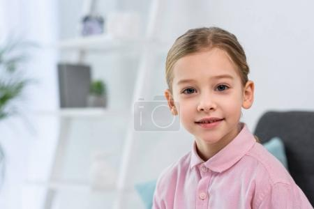 portrait of pretty little child in pink shirt looking at camera at home