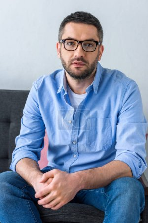 portrait of man in eyeglasses sitting on sofa and looking at camera