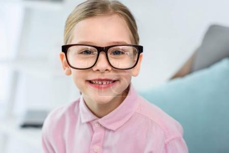 portrait of smiling kid in eyeglasses looking at camera at home