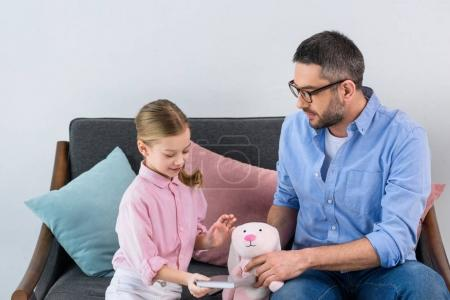 portrait of father playing with daughter with toy on sofa at home