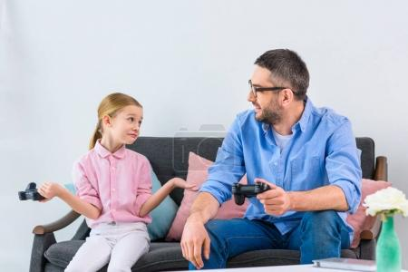 Photo for Daughter and father playing video game together at home - Royalty Free Image