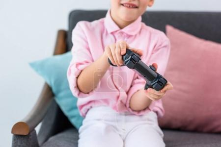 partial view of kid with gamepad in hands playing video game at home