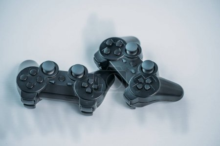 close up view of black gamepads for playing video game on grey tabletop