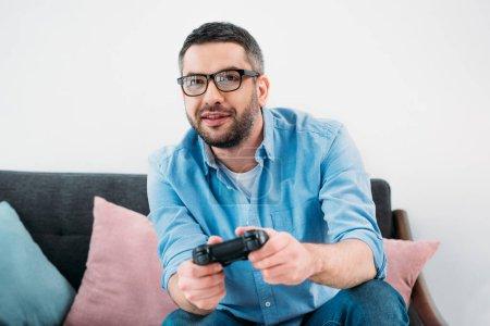 Foto de Retrato de hombre centrado jugando video juego en casa - Imagen libre de derechos