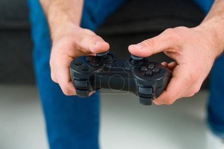 Foto de Vista parcial del hombre juego video en casa - Imagen libre de derechos