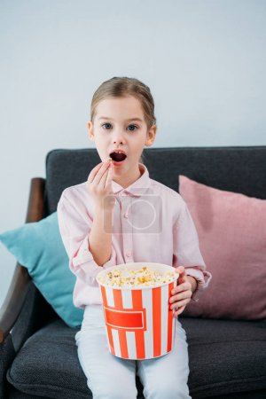 portrait of kid eating popcorn and watching film at home