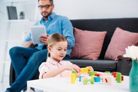 Photo pour Mise au point sélective de l'enfant qui joue avec les blocs colorés tandis que père avec tablette dans le salon - image libre de droit