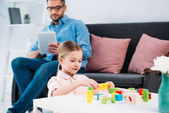 selective focus of kid playing with colorful blocks while father using tablet in living room